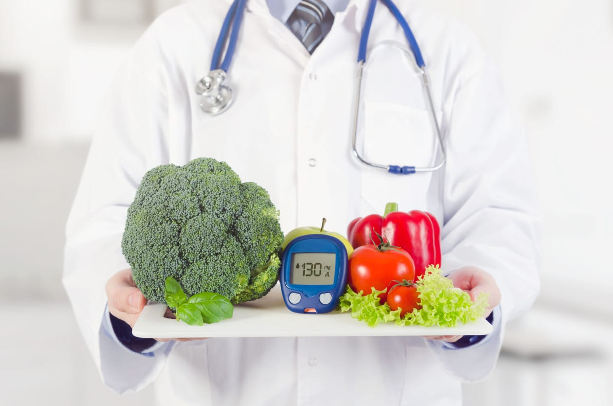 Doctor holding tray of vegetables and a blood monitor